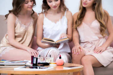 close-up view of cosmetics on table and girls in pajamas reading book behind