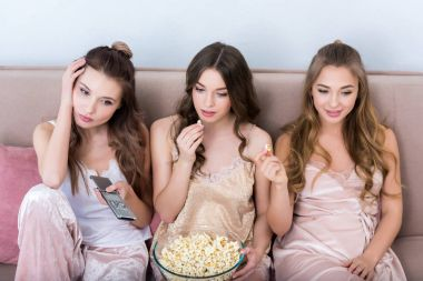 beautiful young women in pajamas eating popcorn and watching tv together at home