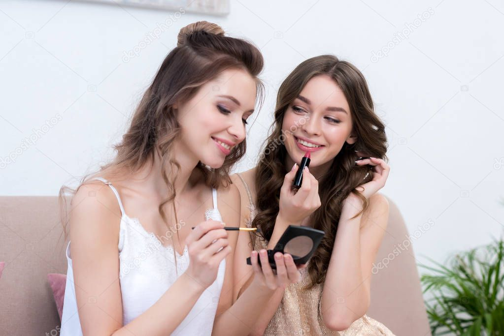 beautiful smiling young women applying makeup together at pajama party