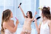 krásné šťastné přítelkyně v pyžamu baví a zpívají s kartáče na vlasy