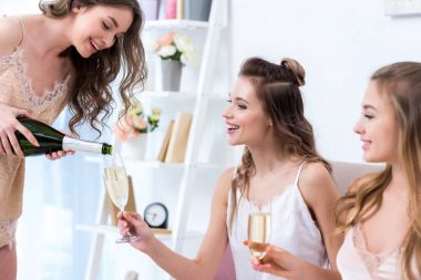 happy young woman in pajama pouring champagne to smiling friends at home