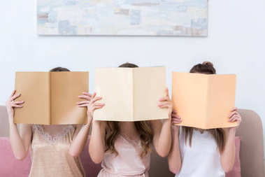 three young women in pajamas hiding faces behind magazines with blank covers