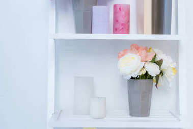 close-up view of white wooden shelves with books, candles and flowers in vase