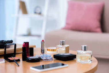 close-up view of smartphone and various cosmetics on table