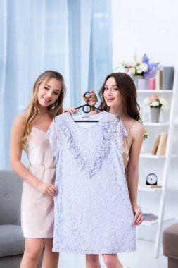 beautiful smiling young women holding hanger with stylish dress at pajama party