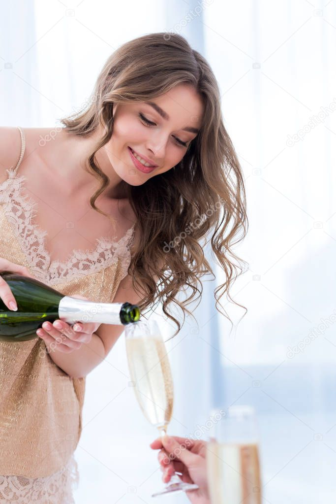 cropped shot of smiling young woman in pajama pouring champagne to girlfriend