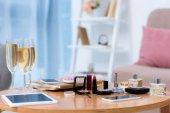 Detailní zobrazení miniaplikací, sklenice šampaňského a různé kosmetiky na stole