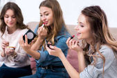 atraktivní usměvavé mladé ženy použití make-up společně doma