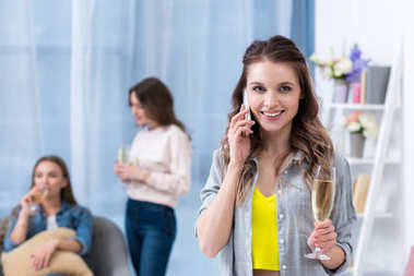 beautiful smiling young woman holding glass of champagne and talking by smartphone while girlfriends spending time together behind