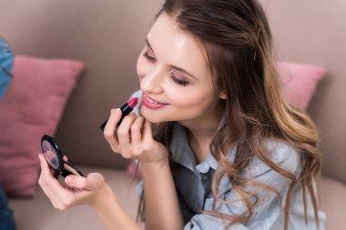 beautiful smiling young woman applying lipstick