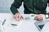 részleges kilátás nyílik üzletember számítások munkahelyen csésze kávé