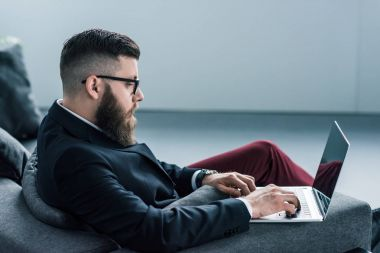 side view of focused stylish businessman using laptop
