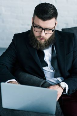 portrait of stylish businessman using laptop