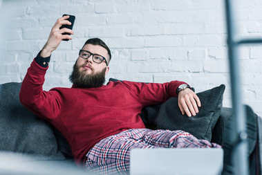 portrait of businessman resting on sofa and using smartphone