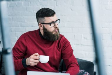 portrait of pensive businessman in eyeglasses with cup of coffee looking away