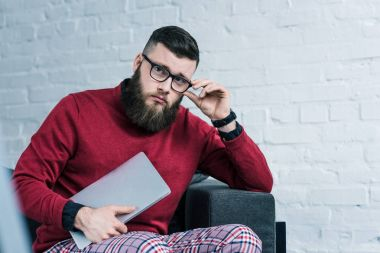 portrait of stylish businessman in eyeglasses with laptop sitting on sofa