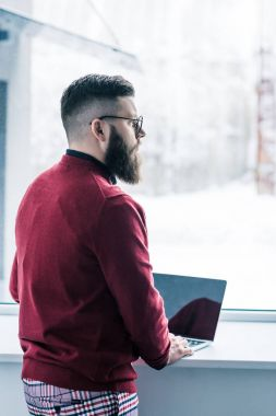 pensive businessman in eyeglasses looking out window while working on laptop