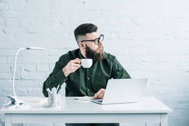 Portrait of pensive businessman with cup of coffee sitting at workplace with laptop stock vector