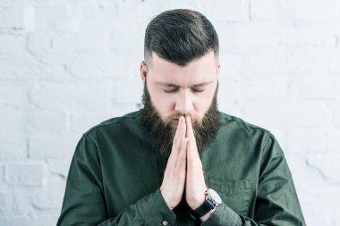 Portrait of stylish bearded man praying against white brick wall stock vector