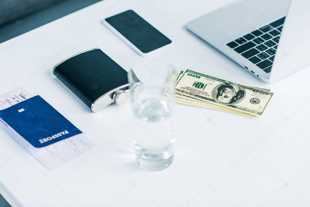 close up view of glass of water, flask, passport with ticket, money, smartphone and laptop on tabletop