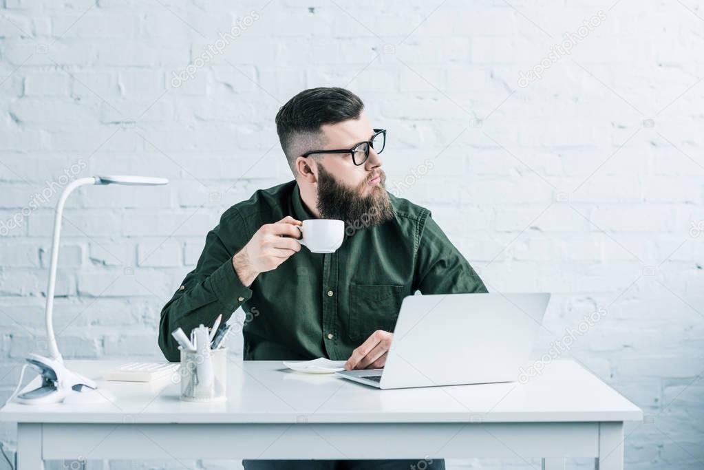 portrait of pensive businessman with cup of coffee sitting at workplace with laptop