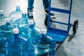 Fotografie Lader Mann mit Lieferung Warenkorb von Wasser in Flaschen stehend