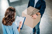 Photo Courier holding box while woman sighing cargo declaration