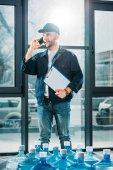 Fényképek Szállítási ember jegyzettömbbel, beszél a telefonon