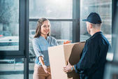 Photo Woman receiving package from delivery man