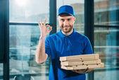 Fotografia Sorridente corriere con pizze in scatole che mostrano segno giusto