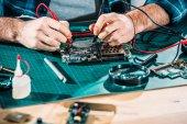 Datailní pohled mužského inženýr pracující s obvodové desky a multimetr