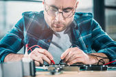 männlicher Ingenieur testet Leiterplatte