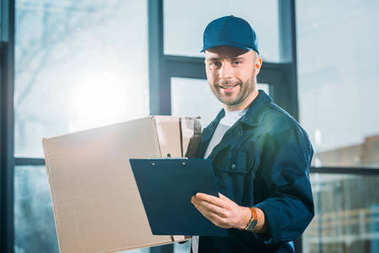 Courier holding cardboard box and cargo declaration