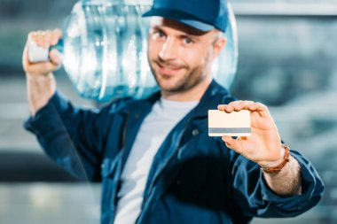 Smiling delivery man holding water bottle and showing credit card stock vector