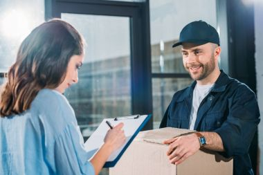 Woman sighing cargo declaration while courier holding box