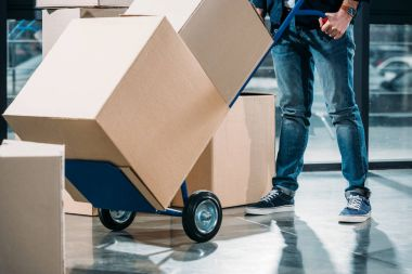 Close-up view of delivery man carrying boxes on cart