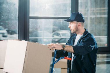 Loader man adjusting cardboard boxes on cart