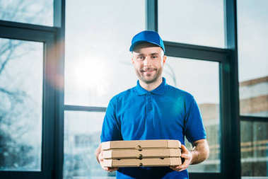 Smiling delivery man carrying pizzas in boxes