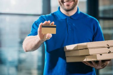 Close-up view of delivery guy with pizzas in boxes showing credit card stock vector