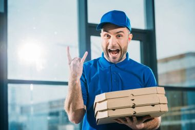 Excited courier with pizzas in boxes showing rock sign
