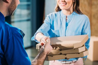 Close-up view of woman holding stack of pizzas in boxes and passing card for courier