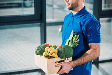 Courier holding box with fresh fruits and vegetables