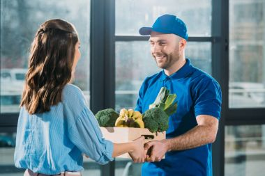 Courier giving woman box with fresh fruits and vegetables