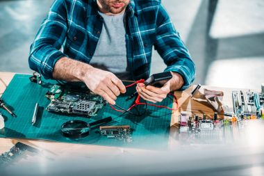 Close-up view of hardware engineer working with multimeter