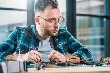 Repairman testing circuit board and checking multimeter measurements stock vector