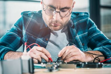 Male engineer testing circuit board