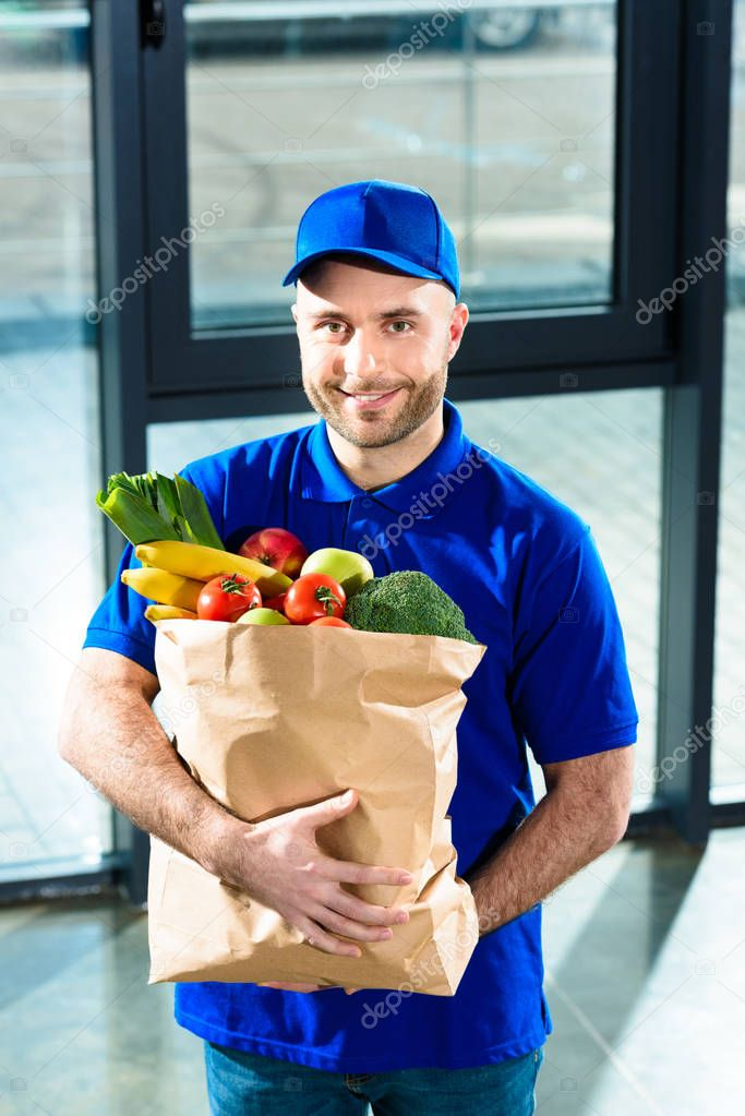 Delivery man holding paper bag with fresh fruits and vegetables