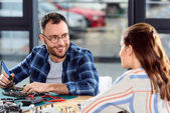 Usmívající se strojní pájení hardwaru a při pohledu na ženské asistent