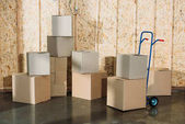 Fotografie Cardboard boxes and hand truck in warehouse room