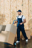 Photo Loader man carrying cardboard boxes on hand truck